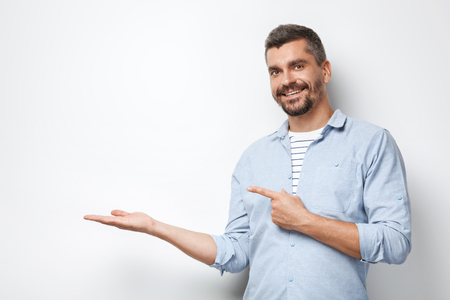 Portrait of handsome caucasian stylish man with grey beard standing on white background. Man pointing at empty white wall