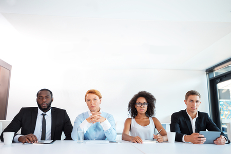 Photo of creative multi ethnic business group. Mixed race business team or commission with electronic devices seriously looking at camera while judging. White modern office interior