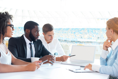 Photo of creative multi ethnic business group. Mixed race business team using laptop and discussing project. White modern office interior with big window Stock Photo