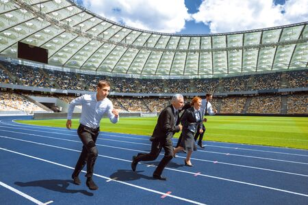 Side view photo of confident multi ethnic business people running to win and cross the finish line on modern sport track.