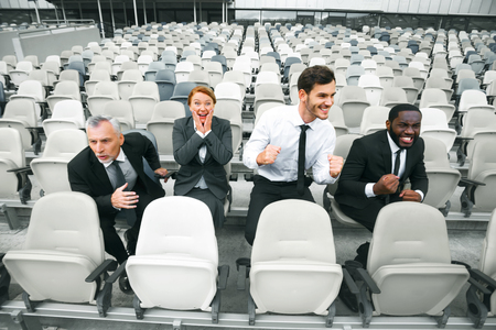 Photo of happy multi ethnic business people. Mixed race business team sitting in row and cheering on modern sport stadium. Stadium seats as a background
