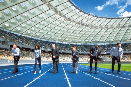 Photo of confident multi ethnic business people standing in row and getting ready for race on modern sport track. Stadium as a background