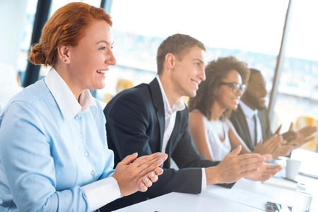 Photo of creative multi ethnic business group. Mixed race business team or commission cheerfully smiling, sitting in row and applauding. White modern office interior with big window