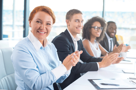 Photo of creative multi ethnic business group. Mixed race business team or commission cheerfully smiling, sitting in row, looking at camera and applauding. White modern office interior with big window Stock Photo