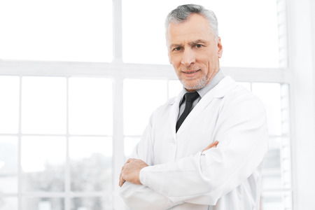 medico: Portrait of aged doctor wearing lab coat. Doctor in years standing in hospital office with big window. Medico smiling and looking at camera Stock Photo