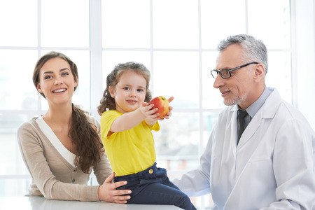 medico: Portrait of aged doctor, little patient and her mother. They are in hospital office with big window. Medico diagnosing little girl Stock Photo