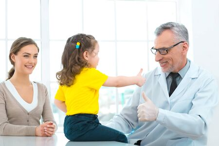 medico: Portrait of aged doctor, little patient and her mother. They are in hospital office with big window. Medico diagnosing little girl. Doctor and girl showing thumb up Stock Photo