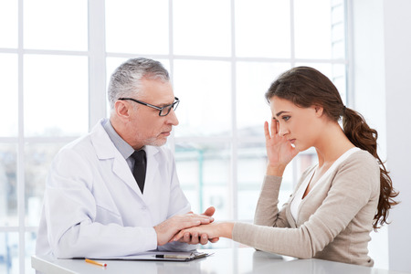 Portrait of aged doctor wearing lab coat. Doctor in years is in hospital office with big window. Medico diagnosing young tired woman Stock Photo