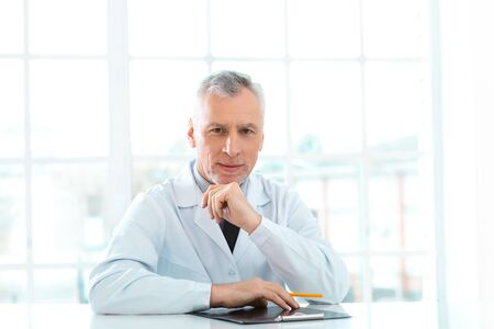 medico: Portrait of aged doctor wearing lab coat. Doctor in years sitting in hospital office with big window. Medico holding folder and looking at camera