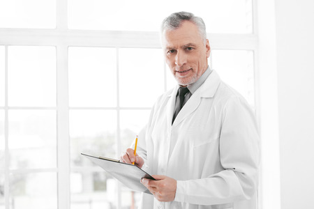 medico: Portrait of aged doctor wearing lab coat. Doctor in years standing in hospital office with big window. Medico holding folder and looking at camera Stock Photo