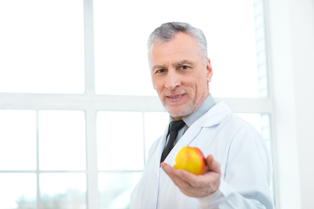 medico: Portrait of aged doctor wearing lab coat. Doctor in years standing in hospital office with big window. Medico holding apple and looking at camera Stock Photo