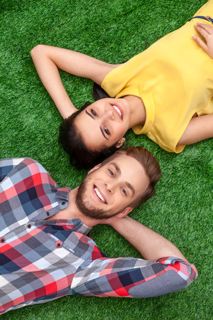 relaxion: Colorful photo of nice couple lying on green grass. Young man and woman cheerfully smiling and looking at camera Stock Photo