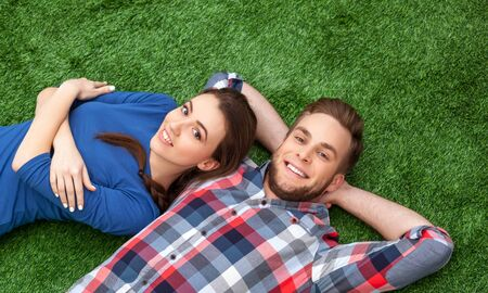cheerfully: Colorful photo of nice couple lying on green grass. Young man and woman cheerfully smiling and looking at camera Stock Photo