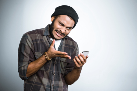 Young mixed race man with beard standing on grey background. Angry young man screaming at mobile phone