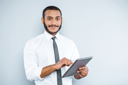 casual business man: Young mixed race businessman with beard standing on grey background. Young man smiling and using tablet computer Stock Photo