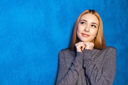 looking aside: Nice portrait of beautiful girl on blue background. Young woman smiling and dreamily looking aside