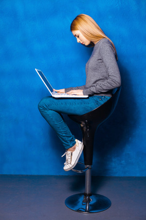 high chair: Nice portrait of beautiful girl on blue background. Young woman sitting on high chair and using laptop