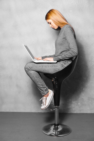 high chair: Nice portrait of beautiful girl on grey background. Young woman sitting on high chair and using laptop Stock Photo