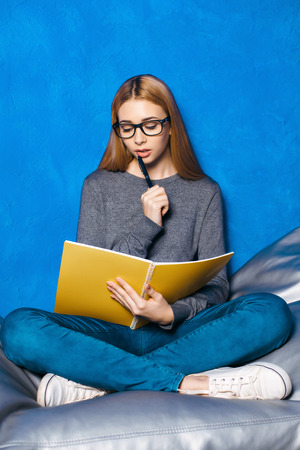 cosily: Nice portrait of beautiful girl on blue background. Young woman with glasses sitting cosily and taking notes Stock Photo