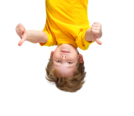 child laughing: Funny photo of handsome little boy hanging upside down on white background. Boy smiling and showing thumbs up Stock Photo