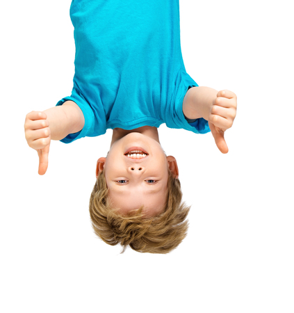 up and down: Funny photo of handsome little boy hanging upside down on white background. Boy smiling and showing thumbs up Stock Photo
