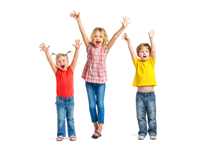 Colorful photo of little boy and cute little girls on white background. Children with hands up looking at camera and cheerfully screaming