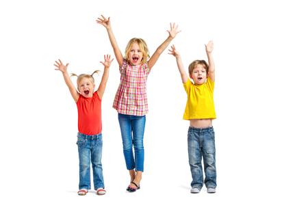 mujer hijos: Foto colorida de niño y niñas lindas en el fondo blanco. Los niños con las manos en alto mirando la cámara y gritando alegremente Foto de archivo