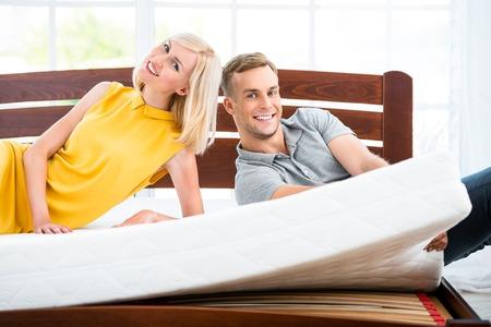 素敵な白いベッドの上に座って愛するカップルの写真。マットレスの品質を示す若い男女 写真素材