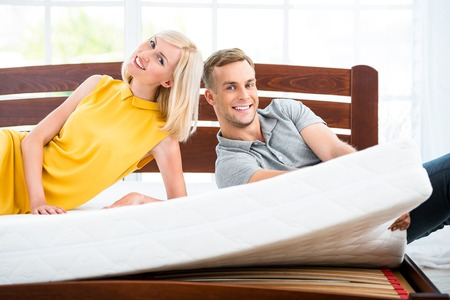 Photo of loving couple sitting on nice white bed. Young man and woman demonstrating quality of mattress