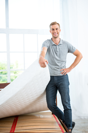 Photo of young man standing near nice white bed. Young man demonstrating quality of mattress