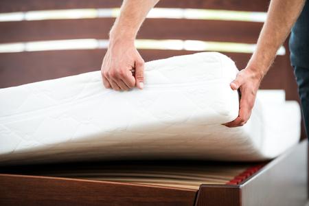 cama: Cierre de la foto del hombre joven que demuestra la calidad del colchón
