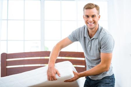 좋은 흰색 침대 근처에 서있는 젊은 남자의 사진. 매트리스의 품질을 보여주는 젊은 남자