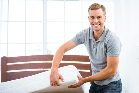 mattress: Photo of young man standing near nice white bed. Young man demonstrating quality of mattress
