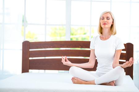 蓮華座で素敵な白いベッドの上に座っている若い女性の写真。マットレスの品質を示す若い女性