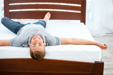 Photo of young man lying on nice white bed. Young man demonstrating quality of mattress