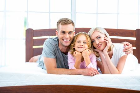세 가지 좋은 흰 침대에 누워의 젊은 가족의 사진입니다. 매트리스의 젊은 가족 보여 질 스톡 콘텐츠