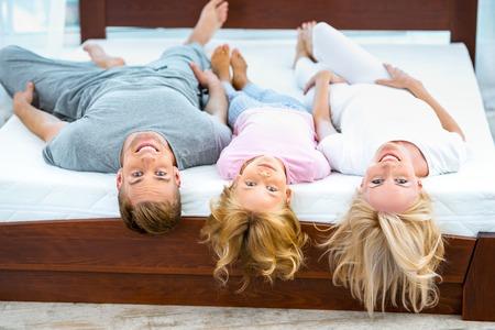 좋은 흰색 침대에 누워 세 젊은 가족의 사진. 매트리스의 품질을 보여주는 젊은 가족 스톡 콘텐츠