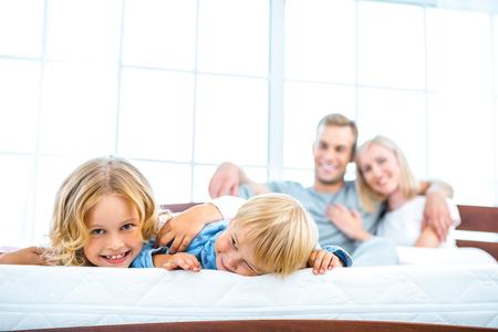 Foto der jungen Familie von vier auf schönen weißen Bett liegen. Junge Familie demonstrieren Qualität der Matratze