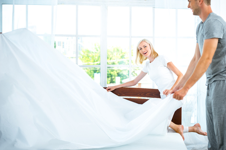 Photo of loving couple making bed. Young man and woman demonstrating quality of mattress and holding blanket