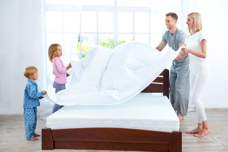Foto von vierköpfige Familie, das Bett zu lieben. Junge Familie demonstriert Qualität der Matratze und Decke halten