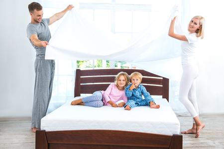gente durmiendo: Foto de amante de la familia de cuatro miembros que hace la cama. familia joven que demuestra la calidad del colchón y la celebración de la manta