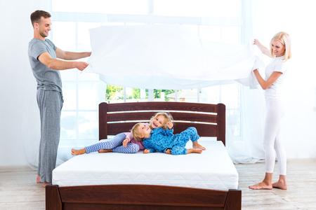 dormir: Foto de amante de la familia de cuatro miembros que hace la cama. familia joven que demuestra la calidad del colch�n y la celebraci�n de la manta