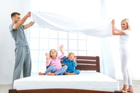 Photo of loving family of four making bed. Young family demonstrating quality of mattress and holding blanket Stock Photo