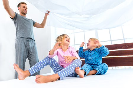 mattress: Photo of loving family making bed. Young family demonstrating quality of mattress and holding blanket
