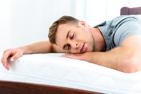 Foto des jungen Mannes auf schönen weißen Bett schlafen. Junger Mann, Qualität der Matratze demonstrieren