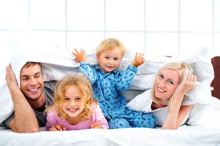 Photo de famille de quatre couché sur un lit blanc le matin aimer. Famille cacher sous une couverture Banque d'images - 49654389