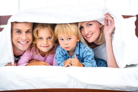 Photo of loving family of four lying on white bed in morning. Family hiding under blanket