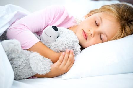 gente durmiendo: Foto de la niña bonita durmiendo en la cama de blanco. Muchacha que abraza el oso de peluche