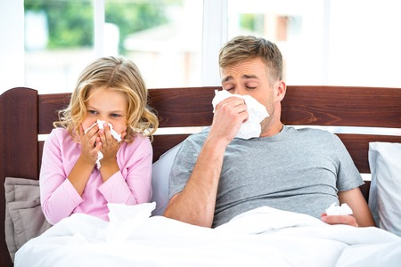 Photo of father and his daughter on white bed in morning. They having runny nose