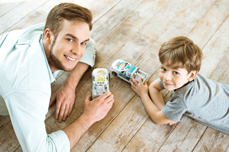 Nice family photo of little boy and his father. Boy and dad playing with cars on wooden floor
